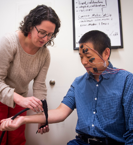 Dr. Lauren Atlas (NCCIH, NIMH, NIDA) applies a thermal heat probe to a volunteer wearing facial electromyography electrodes to measure nonverbal responses to painful stimulation.